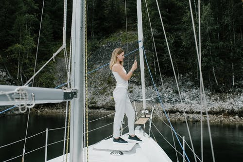 Woman in White Tank Top and White Pants Standing on White Boat