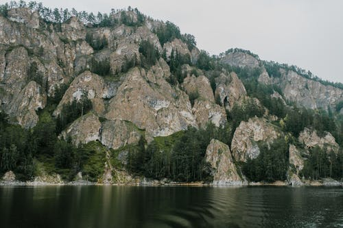 Brown and Green Rock Formation on Body of Water