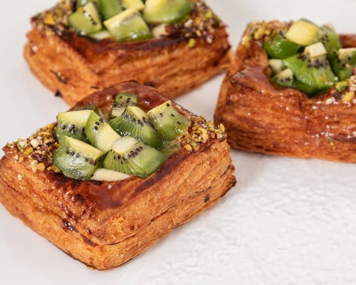 Closeup of golden baked puff pastries with glazed kiwi cubes and crushed nuts