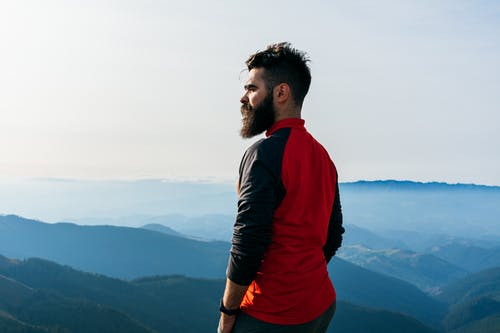 Man in Red and Black Hoodie Standing on Top of Mountain