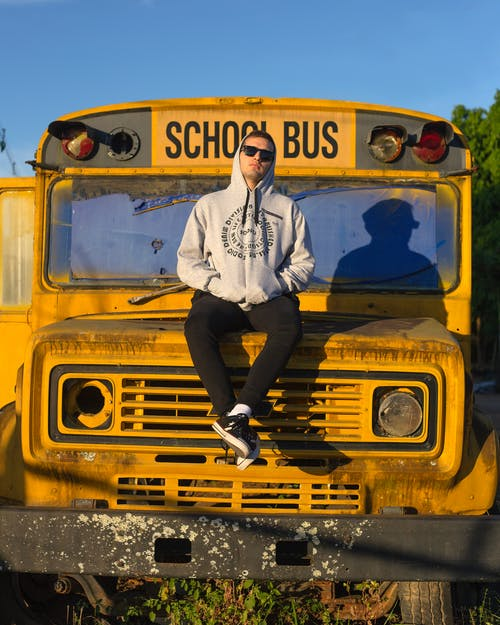 Man in White Dress Shirt and Black Pants Standing Beside Yellow School Bus