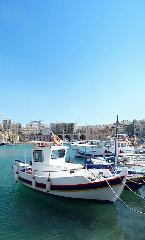 Modern white vessels moored on azure water in port against blue sky in coastal city in summer day in sunlight