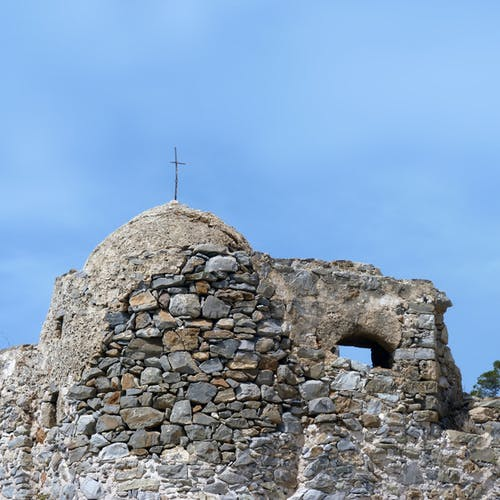 Remains of ancient shabby stone fortress with small cross on top located against blue sky in nature in daylight outside
