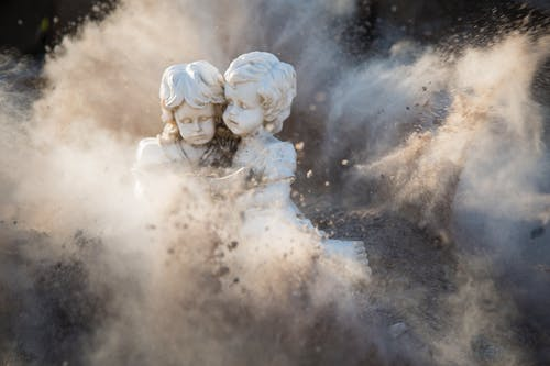 Two White Concrete Statues Covered by Dust