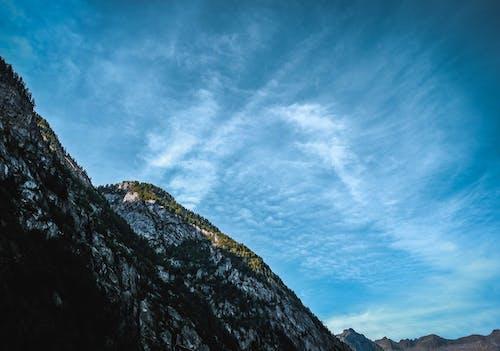High rough mountain under blue cloudy sky