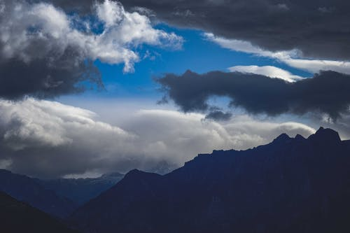 Picturesque view of majestic mount silhouettes with peaks under blue sky with fluffy clouds in evening