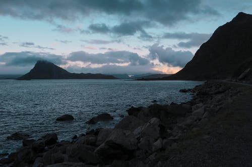 Picturesque scenery of rocky coast of rippling lake and silhouettes of rough mountains