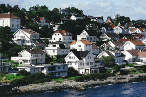 White residential houses located on hill in small town on shore of blue rippling sea