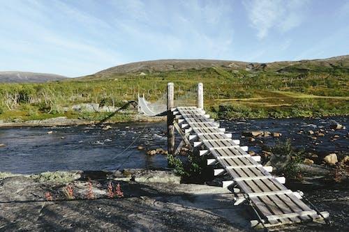 Wooden footbridge over river in hilly valley