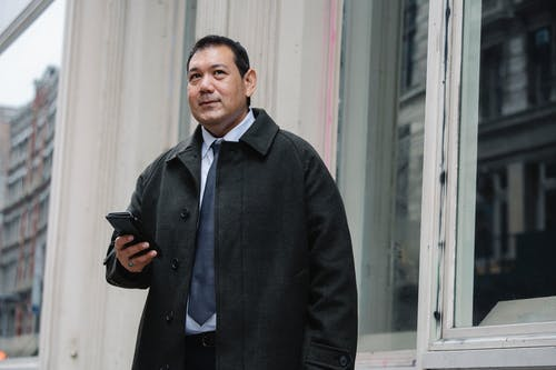 Low angle of confident adult ethnic male manager in classy suit and coat standing on street near building and browsing mobile phone