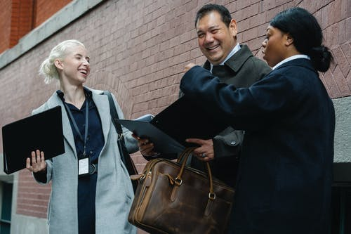 Cheerful multiracial colleagues in formal clothes with documents folders in hands laughing while standing on street after successful workday