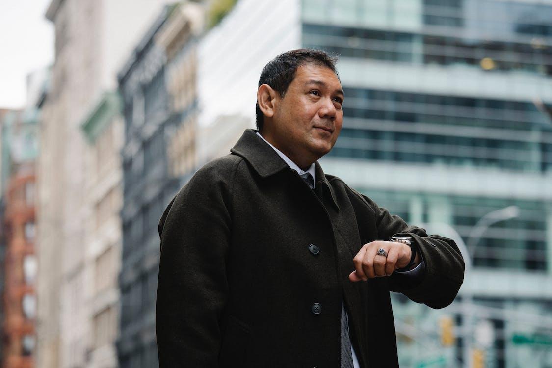 Elegant ethnic businessman checking time on wristwatch on city street