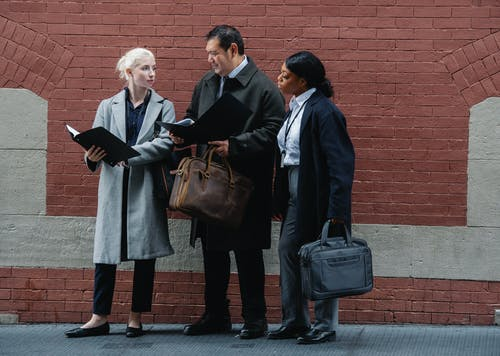 Serious diverse partners examining documents together on city street