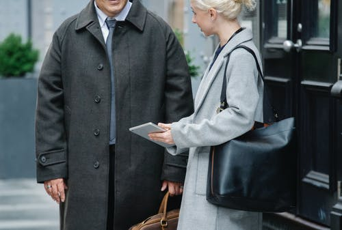Crop woman in elegant coat with bag showing information on tablet to unrecognizable male colleague while standing together on street