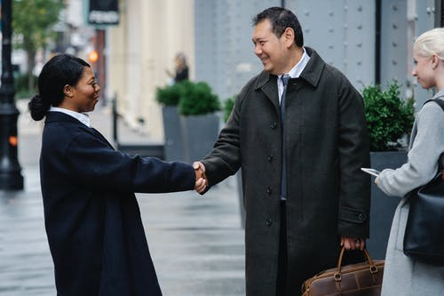 Happy multiracial business partners shaking hands on street after successful deal