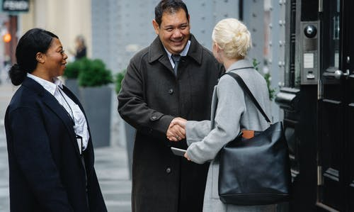 Positive ethnic colleagues greeting anonymous female partner on street