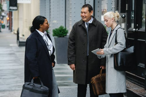 Group of multiracial businesspeople in formal outfits standing on street with tablet and talking about business strategy