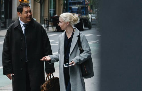 Young woman with blond hair in stylish coat speaking with positive middle aged ethnic male on street