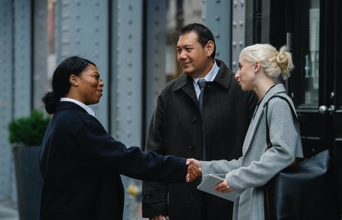 Positive multiracial coworkers doing handshake on street after business meeting