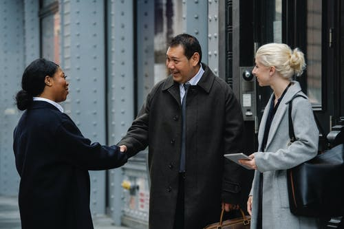 Smiling diverse coworkers shaking hands on street before meeting