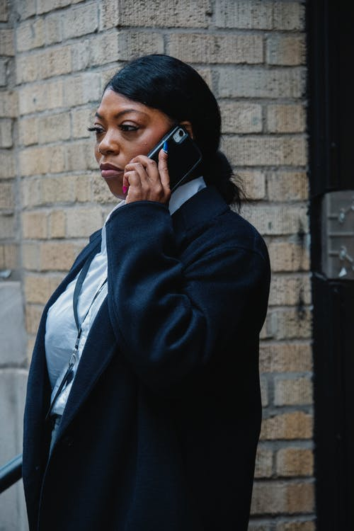 Confident young black female employee talking on smartphone on street