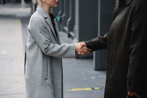Crop anonymous man and woman in elegant coats shaking hands on street while having meeting in city downtown