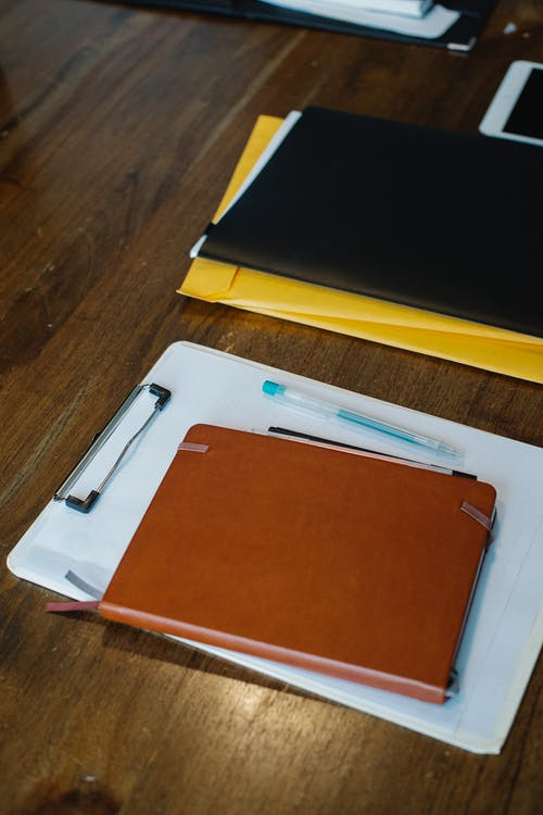 Notebook and clipboard with papers placed on desk with folders and pens