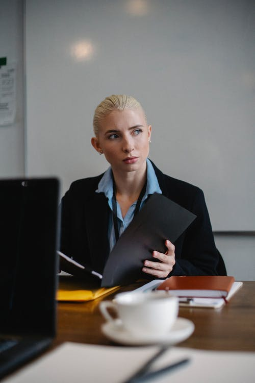 Concentrated young female manager with blond hair in classy outfit sitting at table with documents and looking away thoughtfully