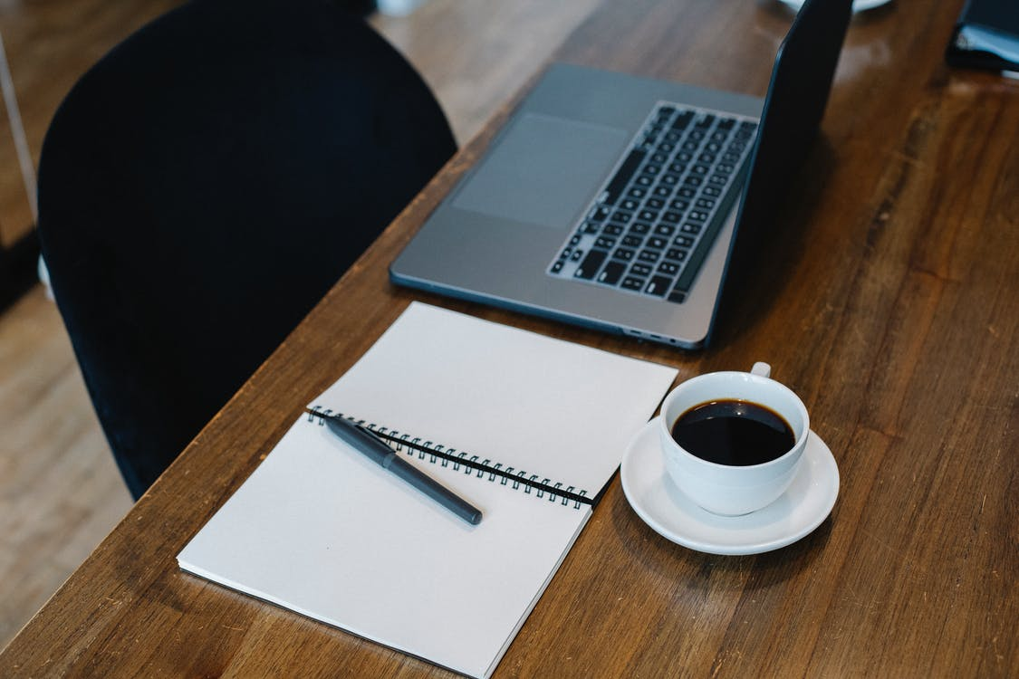 Workplace with laptop and notepad placed near coffee cup