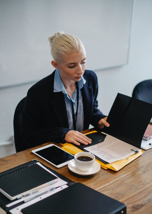 From above of focused young businesswoman in formal clothes reading documents placed in folder while working in office sitting at table with cup of coffee and tablet