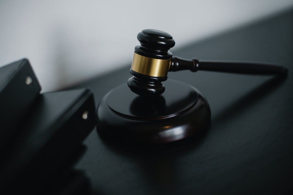 Small judge gavel placed on table. | Photo: Pexels