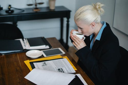 Side view of young concentrated young female judge in formal suit drinking hot coffee while reading case files while sitting at table with stack of documents and tablet