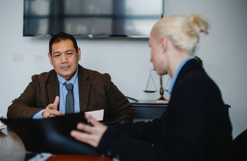 Young female employee with blond hair in classy suit representing project details to middle aged ethnic male manager while working together in office