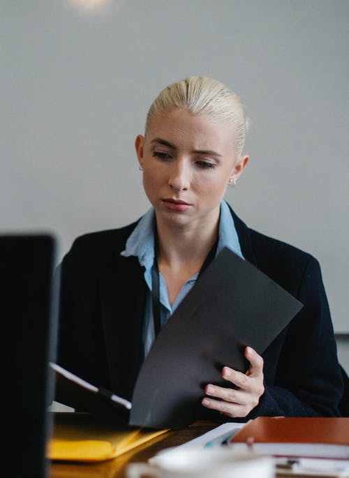 Serious young female employee with blond hair in formal suit sitting at table and reading documents with concentration in office