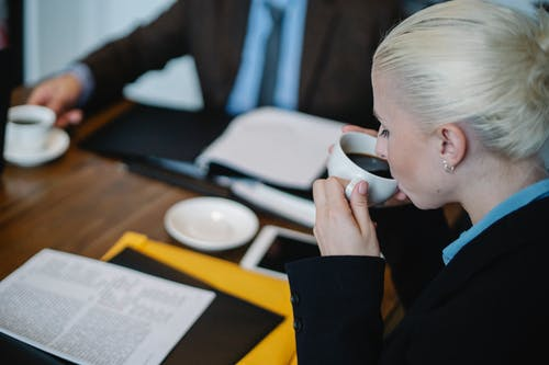 Side view of female in formal clothes drinking hot coffee while sitting at table with documents during business meeting