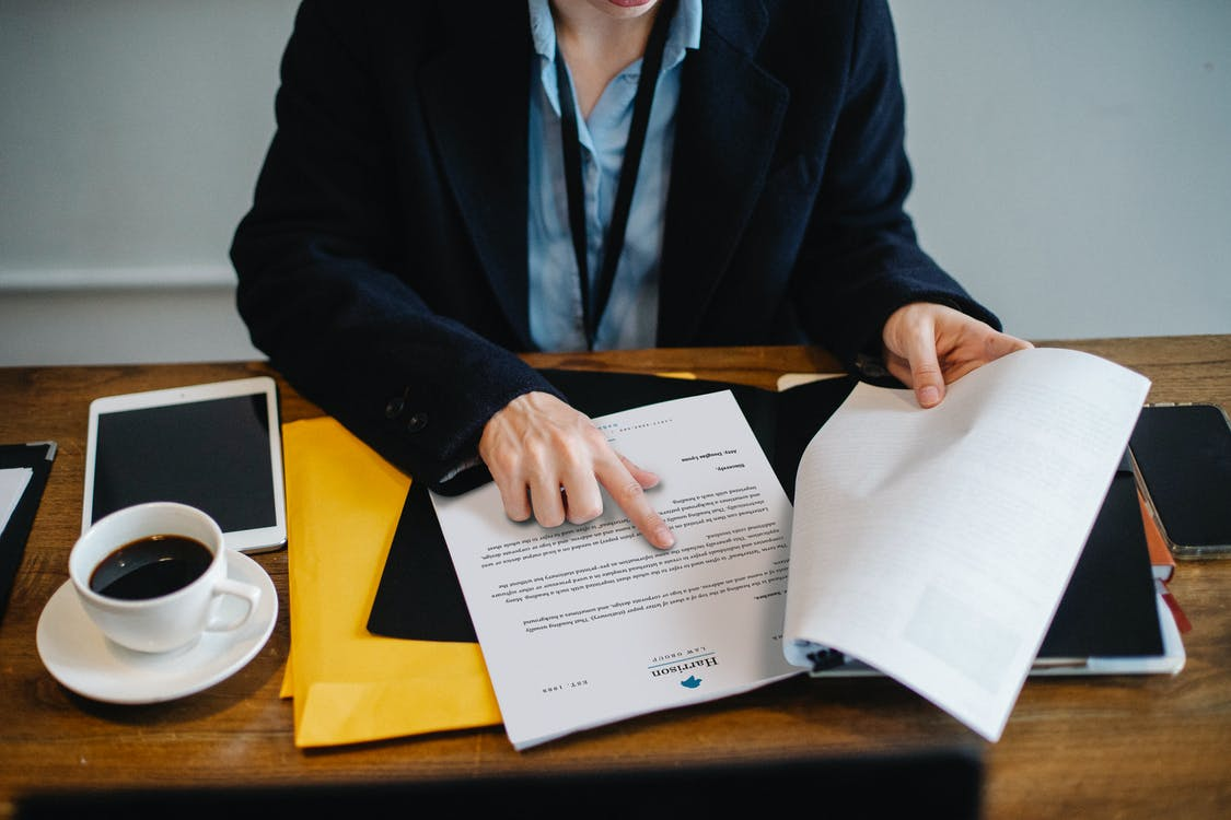 Crop businesswoman working with documents in office