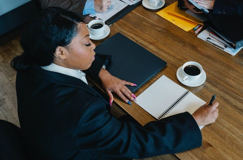 From above of black woman in formal clothes sitting at table during business meeting and writing notes in notebook