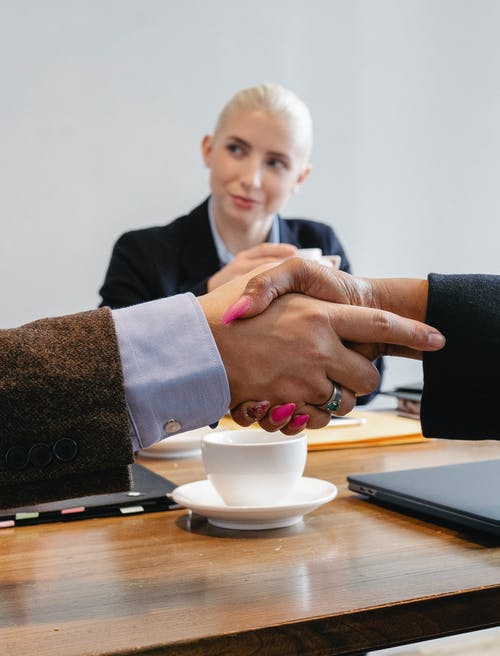 Crop faceless multiracial coworkers sitting at table and shaking hands after successful agreement in workspace