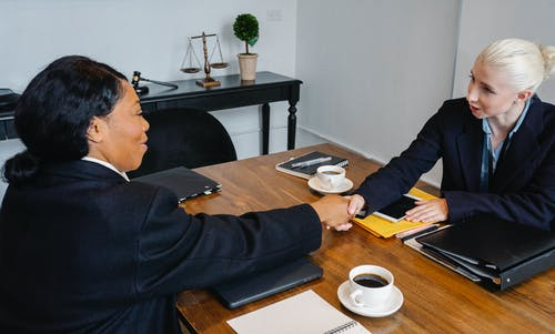 Cheerful businesswomen shaking hands during meeting