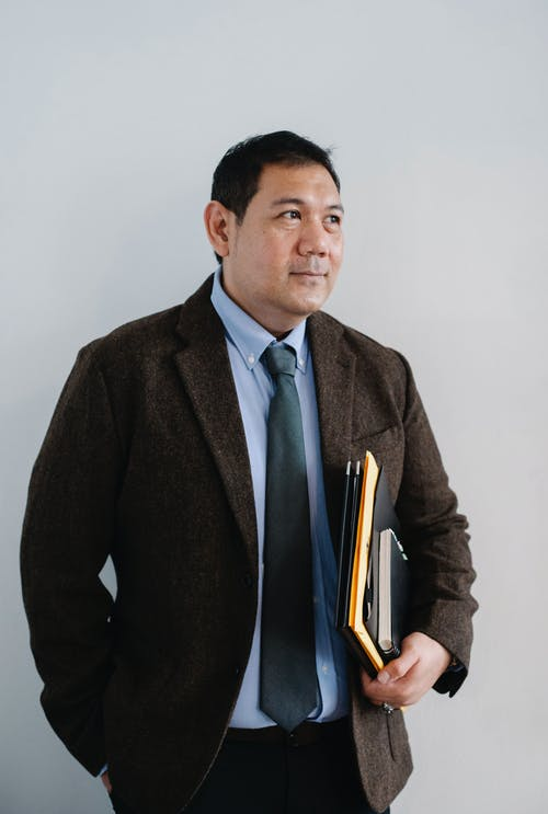 Positive adult ethnic male in formal suit standing with hand in pocket and with paper folders against white wall and looking away