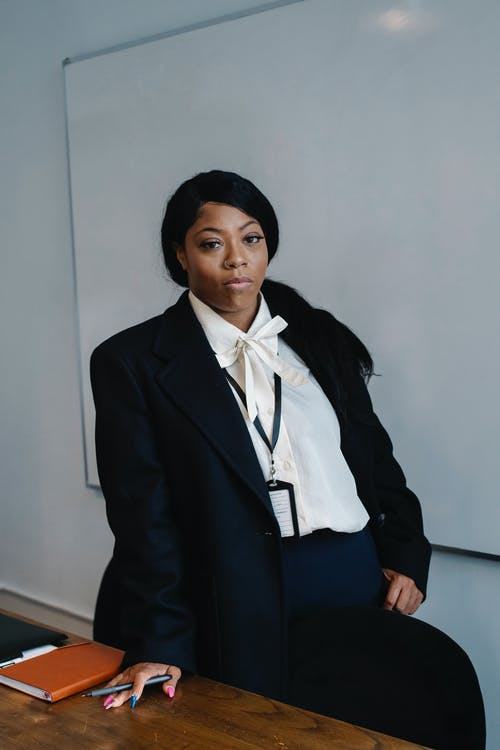 Serious African American female office worker in formal suit standing near table in modern workspace