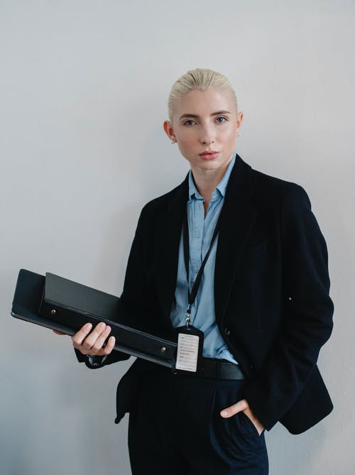 Confident businesswoman standing with folder against white wall