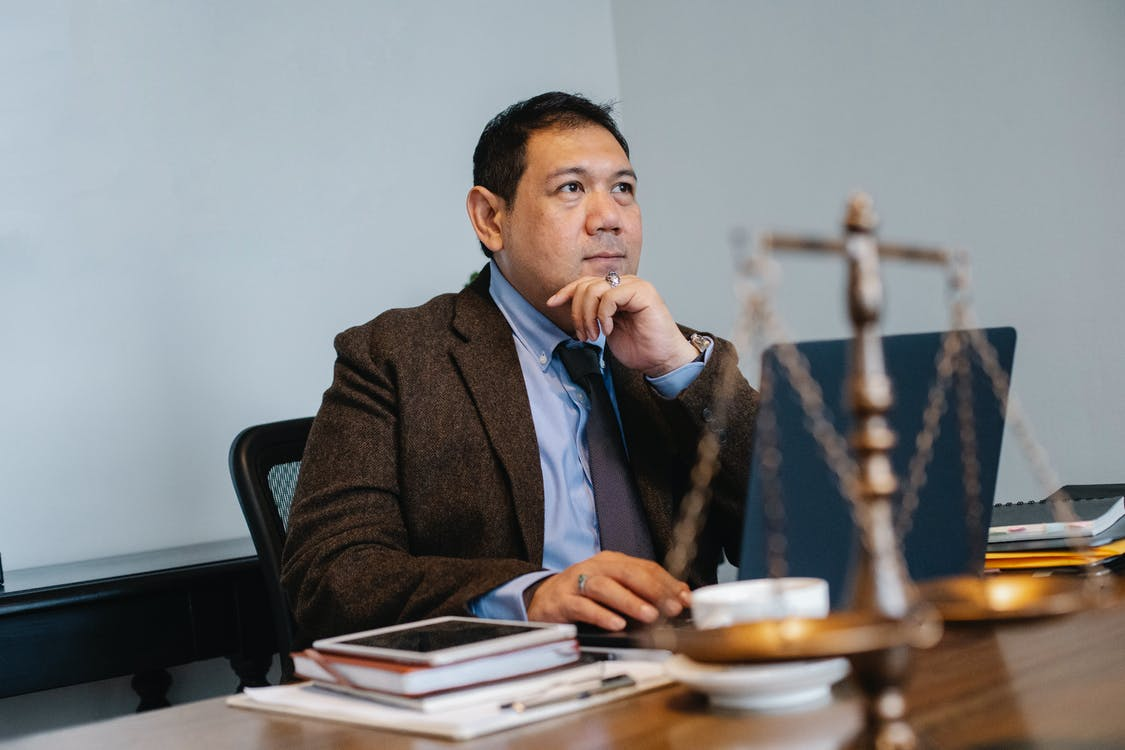 Asian male judge working on laptop in office
