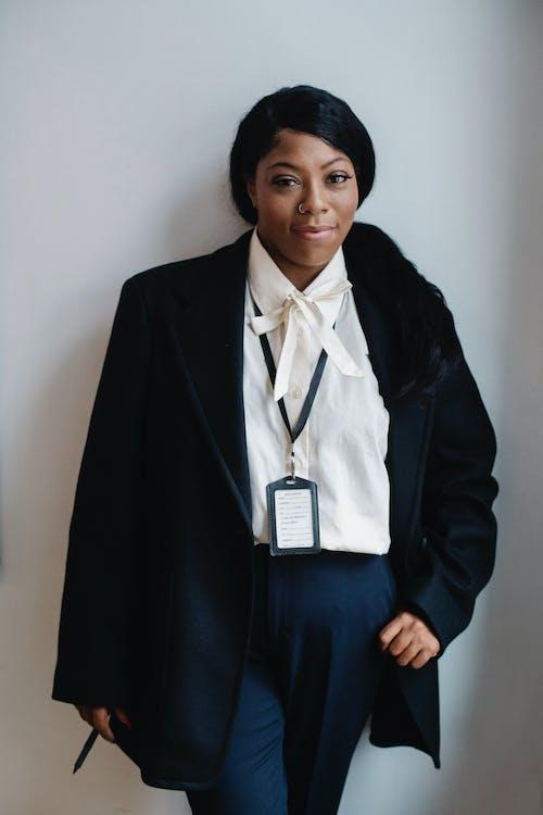 Mulher Negra Positiva Em Um Terno Formal De Pé Contra Uma Parede Branca