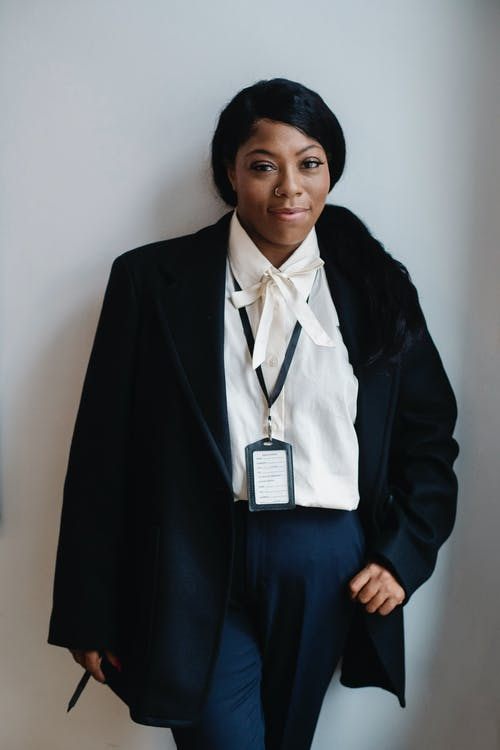 Positive black woman in formal suit standing against white wall