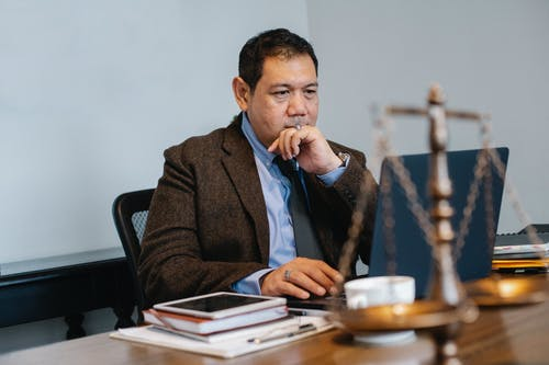 Contemplative Asian lawyer working on laptop in law firm