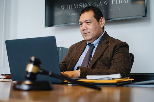 Positive Asian lawyer using laptop in modern office