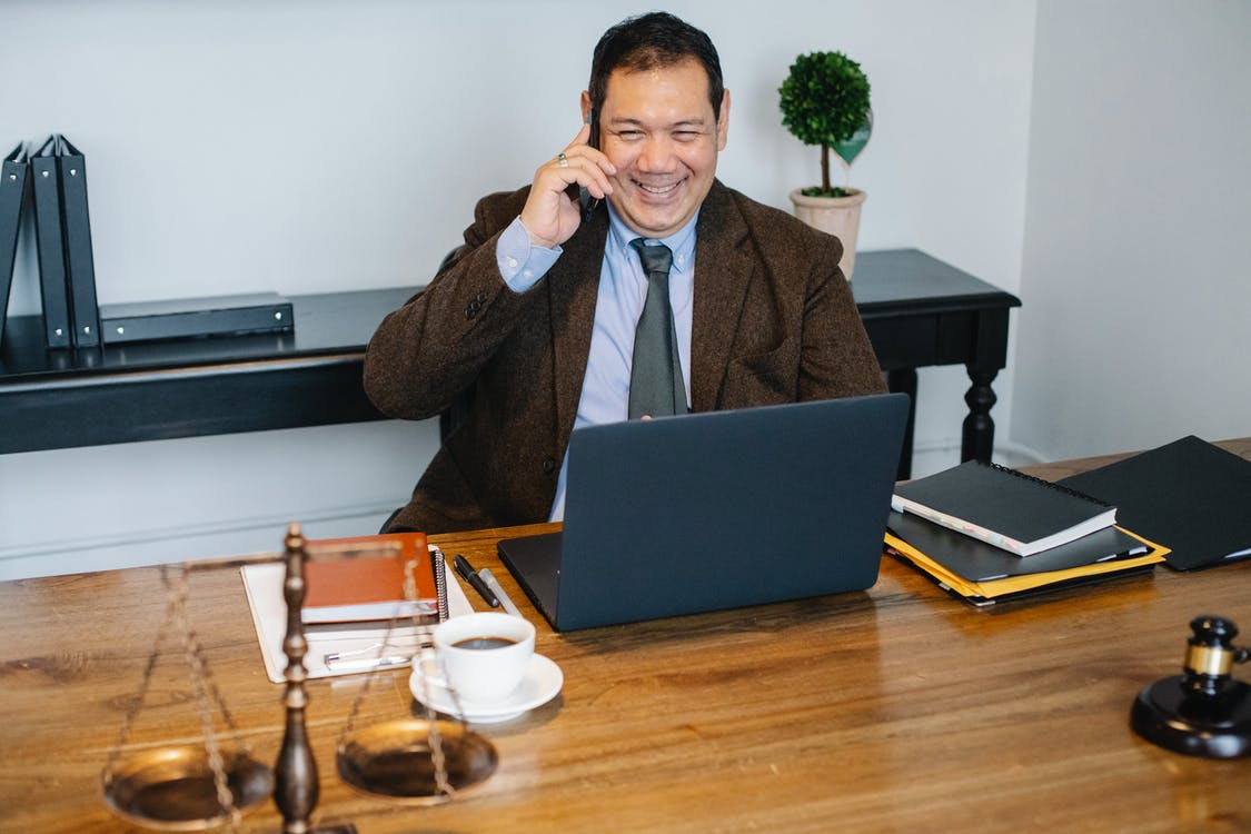 Joyful Asian male lawyer wearing formal suit having conversation on mobile phone and using laptop while working in modern law firm