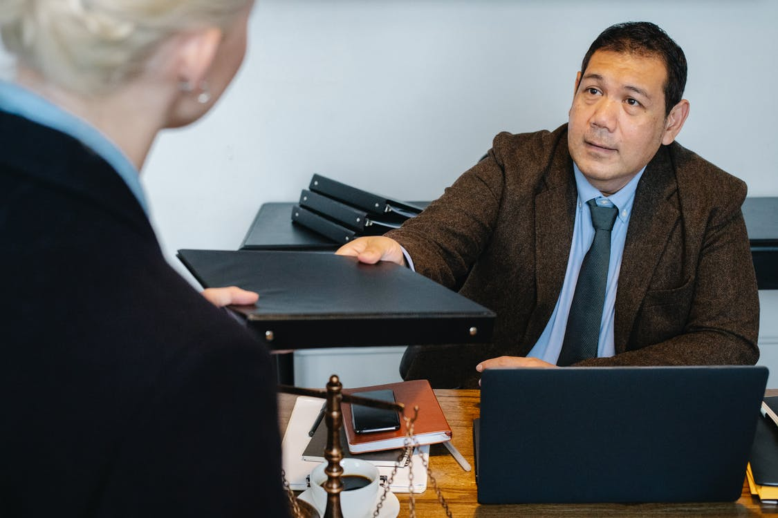 Concentrated ethnic businessman giving folder to female employee in workplace