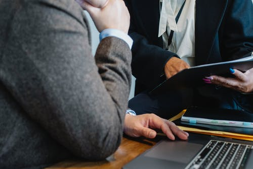 Crop faceless ethnic female entrepreneur in classy suit showing document to anonymous male boss sitting at table with laptop
